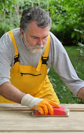 Gold Coast Handyman carefully sanding and preparing a door for repairs and painting